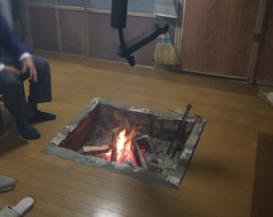 囲炉裏で温まるおじさん